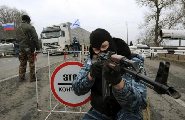 One of the armed men who call themselves members of Ukraine's disbanded elite Berkut riot police …