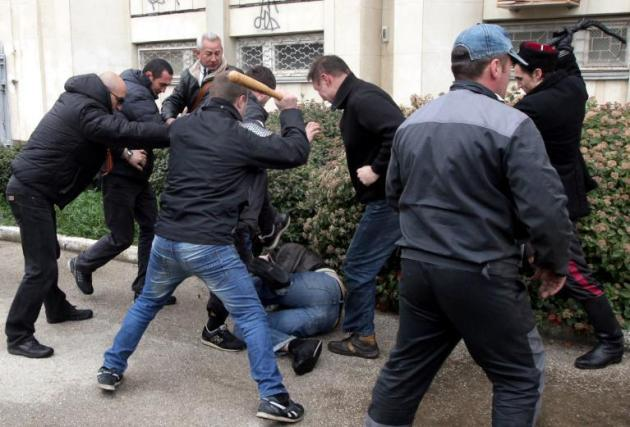 "Pro-Russian ""self-defence"" activists use a bat and a whip to beat a pro-Ukrainian supporte …"