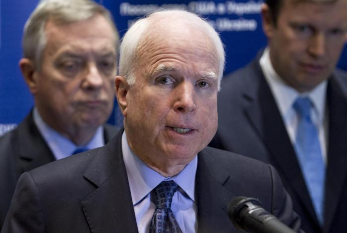 U.S. Sen. John McCain, R-Ariz., center, speaks during a news conference in Kiev, Ukraine, Saturday, March 15, 2014. McCain
