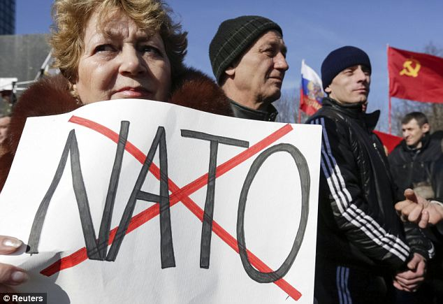 No to Nato: A woman holds a sign decrying the trans-Atlantic alliance, while the Hammer and Sickle, the flag of the Soviet Union, flies in the background at the pro-Russian demonstration earlier today