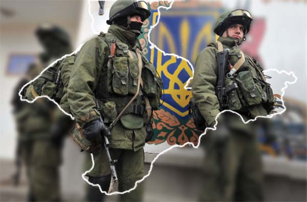 Pro-Russian armed men in military fatigues stand near a painted Ukrainian coat of arms as they block access to a Ukrainian border guard base near Crimea's Perevalnoye on March 2.
