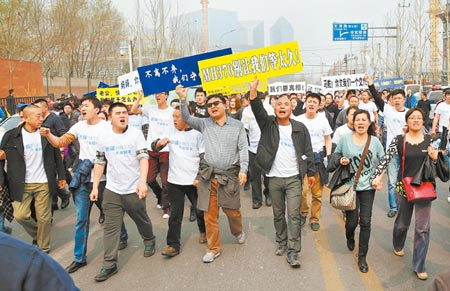 Relatives of flight MH370 passengers take their protest to the Malaysian embassy in Beijing, March 25. (Photo/CNS)