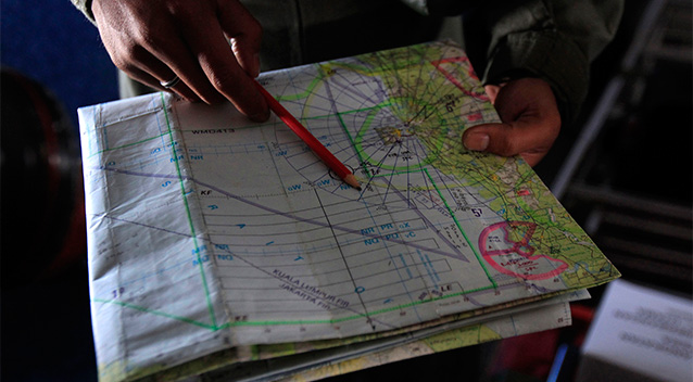A pilot of a Royal Malaysian Air Force CN-235 aircraft shows a map during a search and rescue operation for the missing Malaysia Airlines plane over the waters at Malacca straits. Photo: AP.
