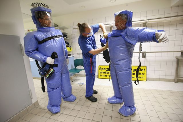 A nurse helps a doctor for tropical medicine and a nurse take off their isolation suits following a demonstration for the media of ebola treatment capabilities at Station 59 at Charite hospital on August 11, 2014 in Berlin, Germany. The specialized quarantine unit at Station 59 is among a handful of facilities in Germany nationwide that are capable of handling ebola cases. According to media reports a German medical student currently in Ruanda is showing signs of the disease, though should he in fact have ebola it is so far unclear whether he would be flown to Germany for treatment. The disease has so far claimed over 1,000 lives in western Africa in recent weeks. (Getty Images)