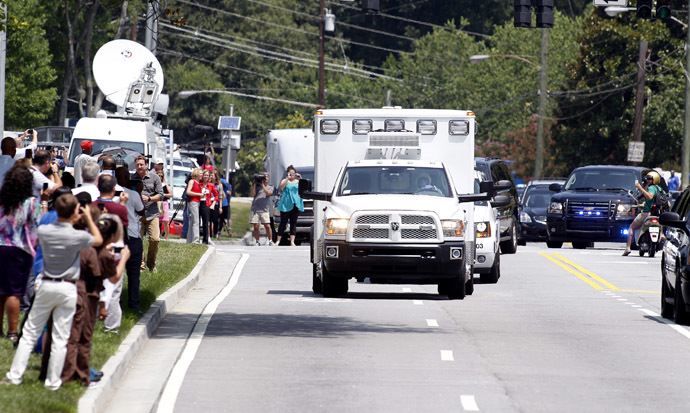 An ambulance carrying American missionary Nancy Writebol, 59, who is infected with Ebola in West Africa arrives past crowds of people taking pictures at Emory University Hospital in Atlanta, Georgia August 5, 2014. (Reuters/Tami Chappell)